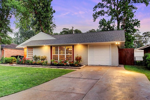 Concrete pavers surround by black crushed granite lead a path to the front porch constructed of flagstone pavers. In true mid century style, a brick accent wall keeps the front door tucked away for added privacy. Two car driveway makes for easy mornings. (photo 2)