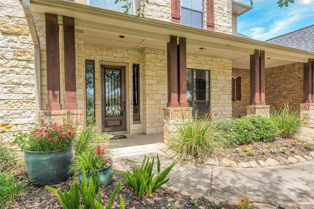 Natural landscaping and plantings line the front walk leading up to the stone front porch and wood & iron front door. (photo 3)