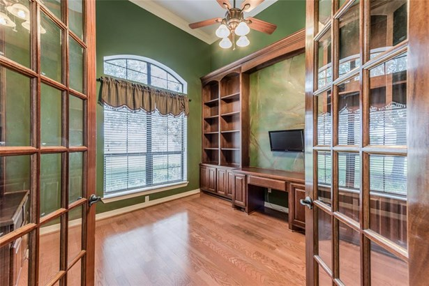 Great private study with glass French door entrance, wall-to-wall built-in desk and storage, ceiling fan and huge arched double window that looks out on the front lawn. (photo 5)