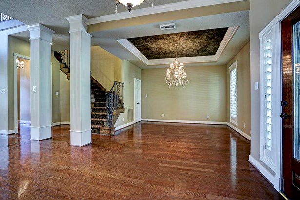 Formal Dining room featuring wood flooring, high ceilings and plantation shutters. Beautiful chandelier and painted coffered ceiling make this a truly elegant entertain space. (photo 3)