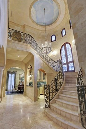 Entering the home, be amazed at the soaring heights and ornate wrought iron railing. Natural light filters through an array of windows and reflects off the gorgeous Italian stone flooring which lend to the feeling of being in an Italian mansion. (photo 3)