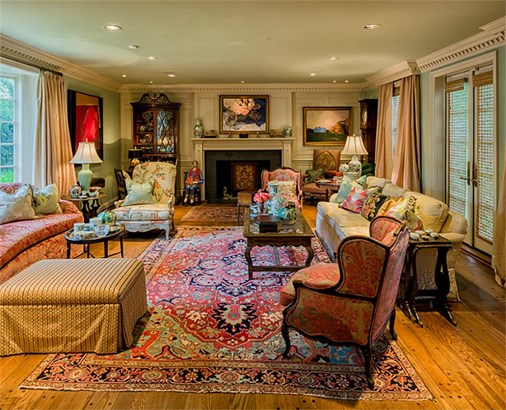 A wood burning fireplace is the focal point in this regal Formal Living Room where the impressive millwork is recurrent. This formal gathering area is light-filled through a bay window to the east, 2 windows & glass-paneled doors to the west. (photo 4)