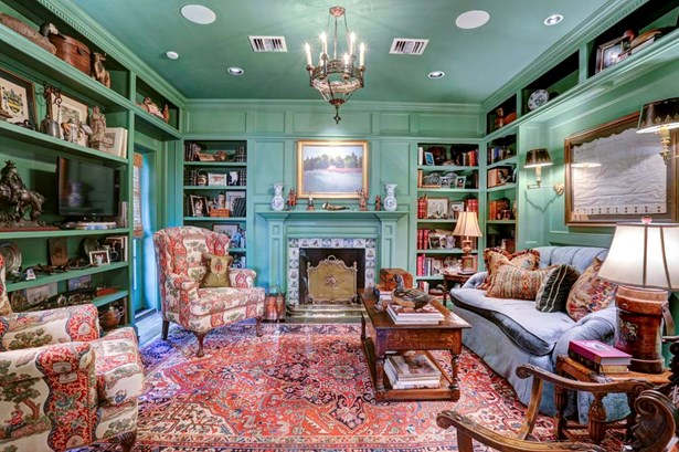 The paneled Library is a focal point from the foyer & features a fireplace with Delft tile surround, walls of shelving, antique Italian light fixture, swing arm reading lamps, glass-paneled doors to the exterior and a window with woven shade. (photo 5)