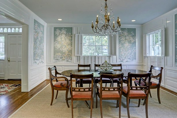 The dining room features a decorative wall covering by Charles Gracie, crown molding, recessed lighting, plantation shutters, and a pocket door to the kitchen. (photo 4)