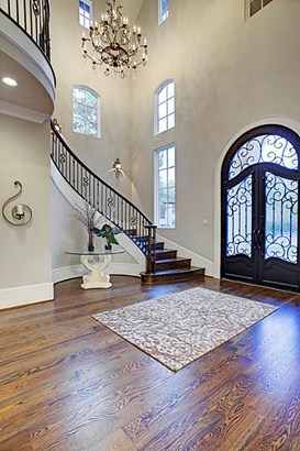 Your grand entrance through the iron and glass doors opens to the two story foyer with a beautiful over-sized chandelier. (photo 3)