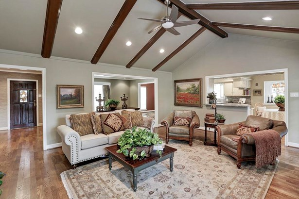 The family room/den features raised, beamed, cathedral ceilings for an air of real spaciousness. This is the view from the rear of the house looking back to the front...including the foyer and formal areas. Recessed lighting throughout. (photo 4)