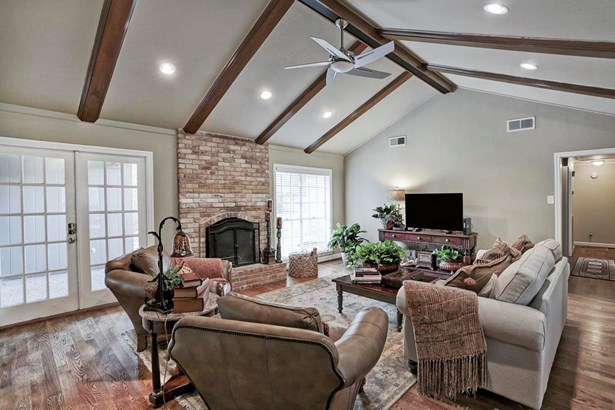 Another view of the family room/den showing the rear of the home where the fireplace is flanked by windows and a doorway out to the rear patio. (photo 5)