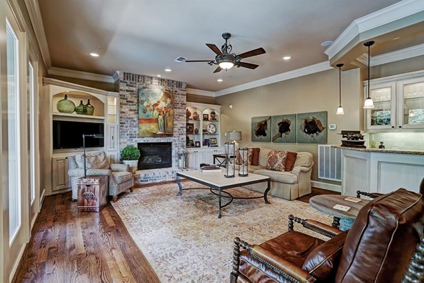 The den is an inviting space with a gas log fireplace with brick surround from floor to ceiling. On either side it is flanked by lit shelves with cabinets below. There is a pull out drawer for CD storage. (photo 5)