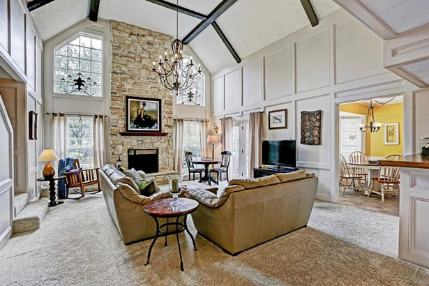 """The """"great room"""" style living area is the center of the house. Such a beautiful room with the beamed ceilings, block paneling, stone fireplace, and the replaced Pella windows. The lovely iron chandelier really makes the room and remains. (photo 2)"""
