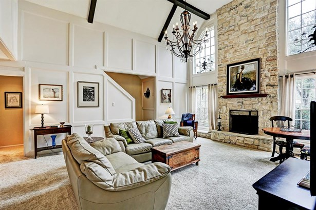 """Another view of the """"great room"""" showing again the wonderful stone fireplace/hearth flanked by the traditional style, high quality Pella windows. Against this wall of block paneling, one can see the discreet staircase going up to the second level. (photo 3)"""