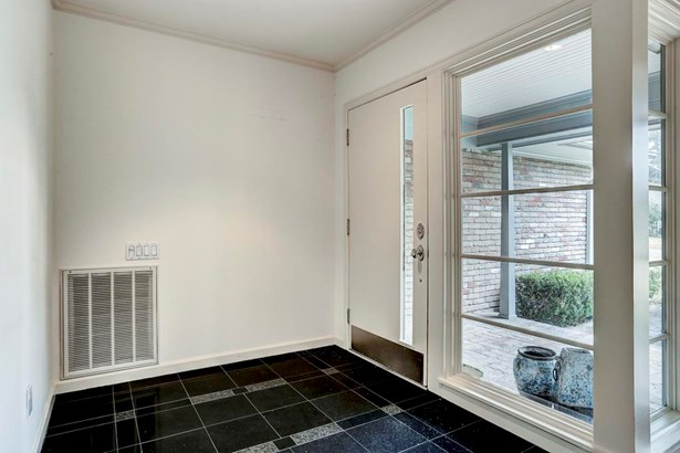A granite tile entry welcomes you into the home. Mid-century appointments like these corner windows add charm to the home. (photo 5)