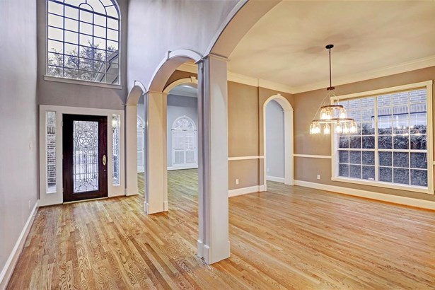 Walk into this beautiful entry which features two story ceilings with windows surrounding that bring in tons of natural lighting. The formal living room flows seamlessly into the formal dining room. (photo 2)