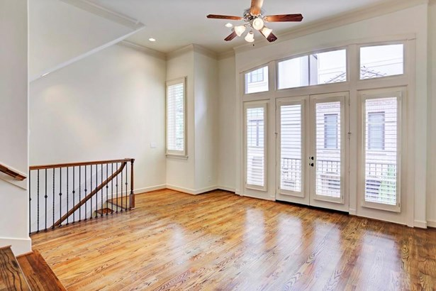 Second floor formal living with beautiful hardwoods and wall to wall windows, plantation shutters all open to a nice size balcony (photo 4)