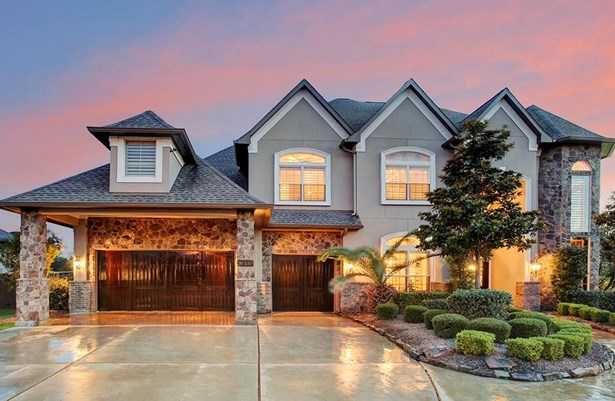 Nestled in the gated community of the Estates of Woodcreek Reserve, this home promotes style and comfort through its exterior of brick and stone. 3 car wooden garage door with automatic openers. (photo 1)