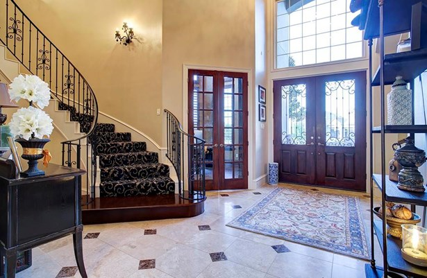 Once inside the double front doors you are greeted by an inviting entry. Rounded staircase black crystal wall sconces and chandelier. Hand painted gold leaf detailing accents the opening to the formal living. (photo 3)