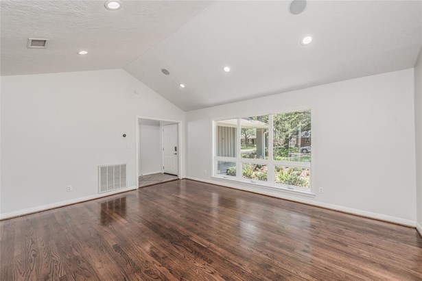 Alternate view of the living room toward the entry, with triple divided windows overlooking the front yard and fresh landscaping. (photo 5)
