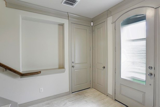 Upon entry you are greeted by stone flooring, two storage closets, garage access and an elevator shaft to all three floors. The neutral tones, base board & crown molding are carried throughout the home. (photo 4)