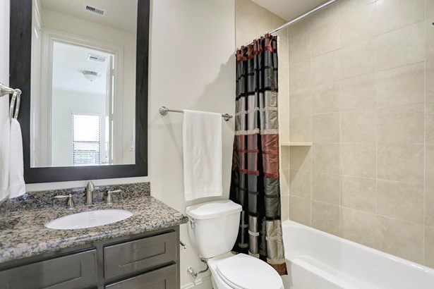 The en-suite bath to the first floor bedroom has a shower/tub combo, vanity with granite countertop, and a dark framed mirror to compliment the vanity. (photo 5)