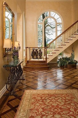Entry with custom design oak hardwood floors and large arched window at front stairs overlooking backyard. (photo 2)