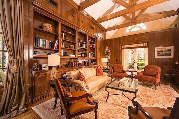 As you enter this magnificent home, step into the formal living room/library with beautiful vaulted ceilings + wood beam accents, and wood paneling. (photo 4)