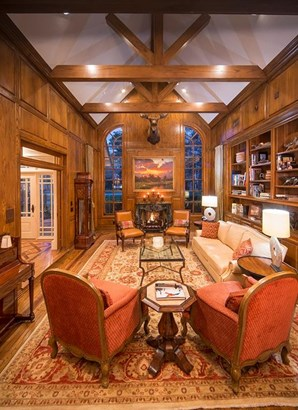 The formal living room/library also offers view of the front grounds and features a wood-burning fireplace. (photo 5)
