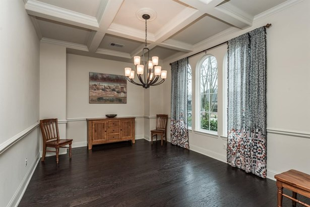The formal dining room has great architectural interest with beamed ceiling details, chair rail and triple arched windows overlooking the front lawn. (photo 3)