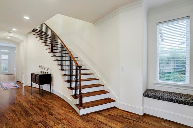 [Foyer]Light-filled foyer transitions into a wide central hall that travels to the great room at the rear. Note red oak floors, 10 -foot to 11-foot ceilings, gently curving staircase with custom balustrade, and window seat. (photo 3)