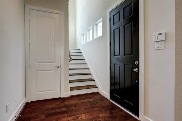 Opposite perspective of the 2 level entry way. Open and bright, stairwell with wooden treads and wooden handle leads guests and residents to the 2nd level. Located directly underneath the stairhall you find a large storage closet. (photo 4)