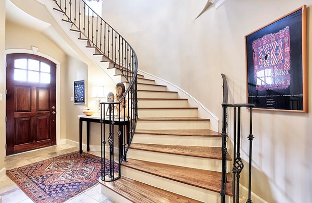 The entry makes a grand impression with its travertine floors, sweeping circular staircase, natural light and one of a kind chandelier. There are 2 coat closets, one of which is the elevator shaft. (photo 3)
