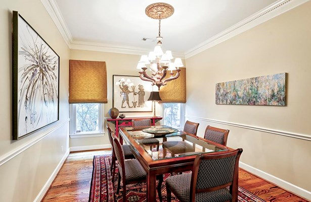 The formal dining room is open to the living room. Its windows overlook greenery as there is space between this property and the home next door. Note the chair rail and crown molding which grace the room. (photo 4)