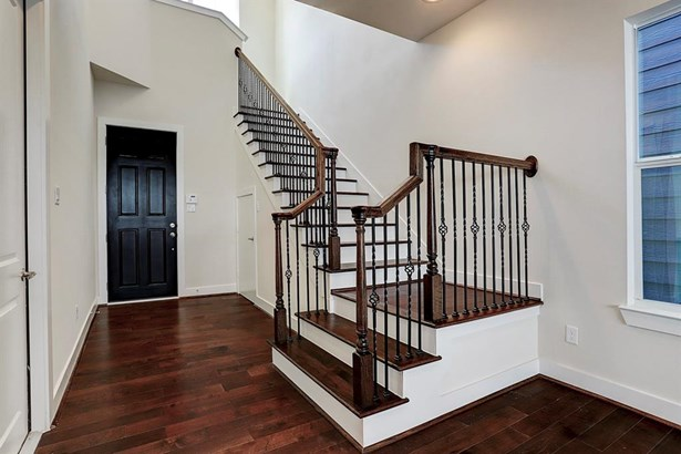 Opposite perspective of the 2 level entry way. Open and bright, stairwell with wooden treads, wrought iron balustrade and wooden handle leads guests and residents to the 2nd level. Located directly underneath the stairhall you find a large storage closet. (photo 5)