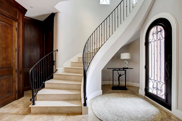 This former model home has exquisite finishes everywhere the eye falls. The Entry Foyer has paneled walls and travertine floors. (photo 3)