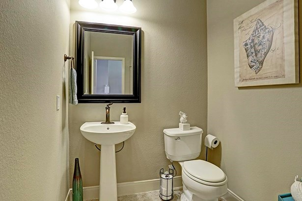As you move down the main hall toward the rear of the home, there is this nicely located and private formal powder half bath featuring designer pedestal sink and commode fixture. Notice the nice wide baseboard moldings and tile flooring. (photo 5)