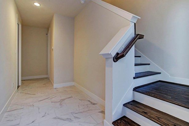 Photo of a similar completed home in another community completed by City Choice Homes. Through the entry door with glass casement guests and residents are greeted with contrasting marble look porcelain and handsomely stained Oak wood that leads you to the (photo 3)