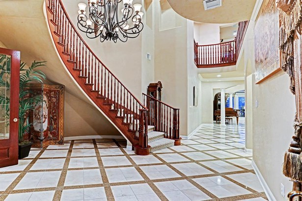 The foyer has inlaid marble floors, chandelier, and dramatically winding staircase. (photo 5)