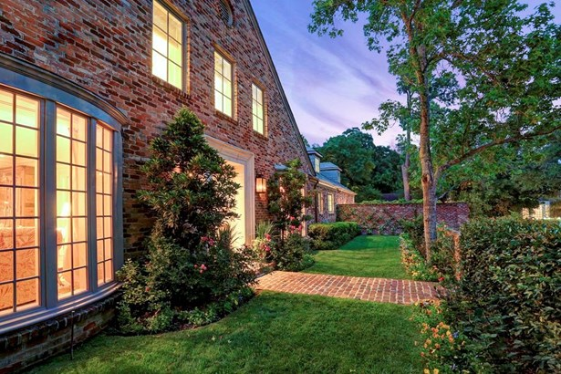 An inviting front with charming brick paver walk, brick wall, iron gate, and colorful landscaping is not only welcoming, but breathtakingly beautiful, too. (photo 2)