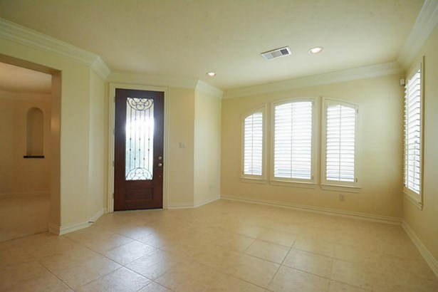 Front door enters to living room. Tile flooring and crown molding throughout first floor. (photo 4)