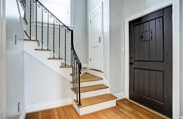 The staircase leading to the second floor has a detailed iron railing and a storage closet. There is also a rustic solid wood front door with peep door. (photo 3)