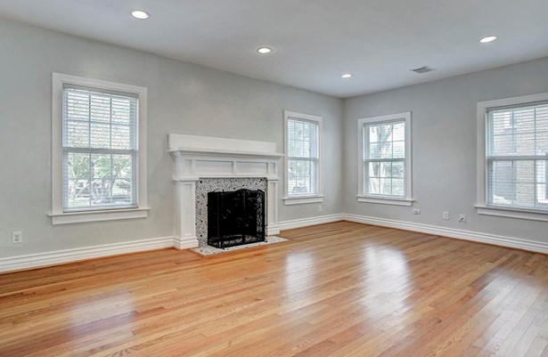 The spacious living room is to the left of the entry and features hardwood floors, a gas fireplace with stone surround and gorgeous mantel, double pane windows and window coverings. The window placement allows for natural light to flood the space. (photo 4)