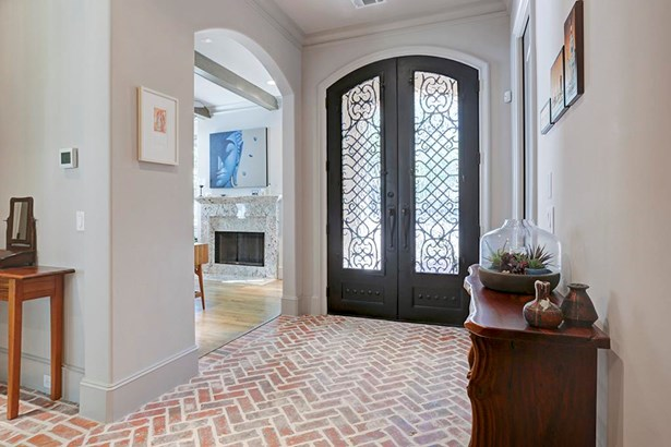 Entry with herringbone pattern brick flooring, heavy wood doors with wrought iron inserts. Powder room on the right and study on the left. Note the curved arches and bullnose corners on sheet rock. (photo 3)
