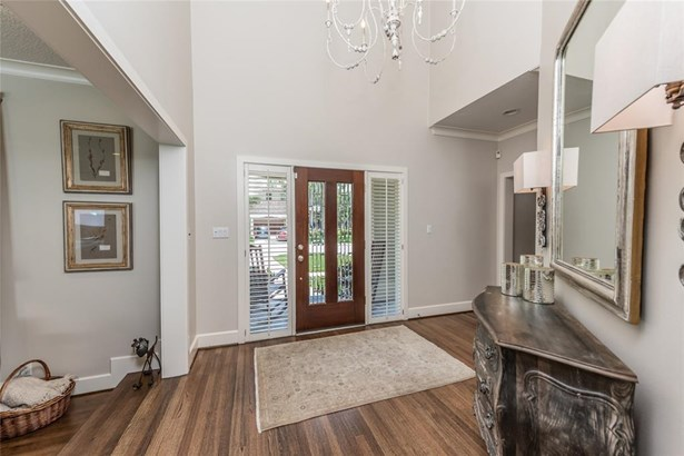 Wood and glass door opens to 2-story entry with accent chandelier and a step-down to the formal living on the left and door opening to the formal dining on the right. (photo 4)