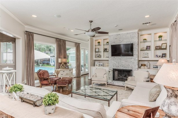 Gorgeous light-filled living room with refreshing outdoor view to the pool and back yard. Wood floors, recessed lighting, ceiling fan, crown molding, and washed brick gas fireplace with built-in storage and lighted upper shelving on each side. (photo 5)