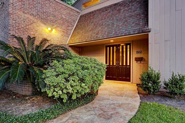 The double-door grand entrance is further tucked behind the landscaped front courtyard. (photo 3)
