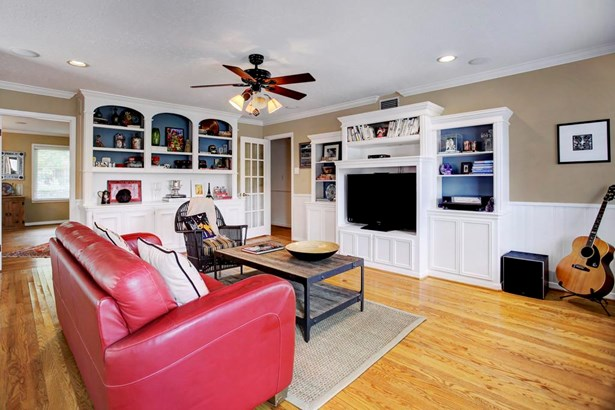 Large family room/den with hardwood floors, crown moldings, recessed lighting, ceiling fan w/lighting and two walls of built-in bookshelves and cabinets. Plentiful storage! (photo 4)