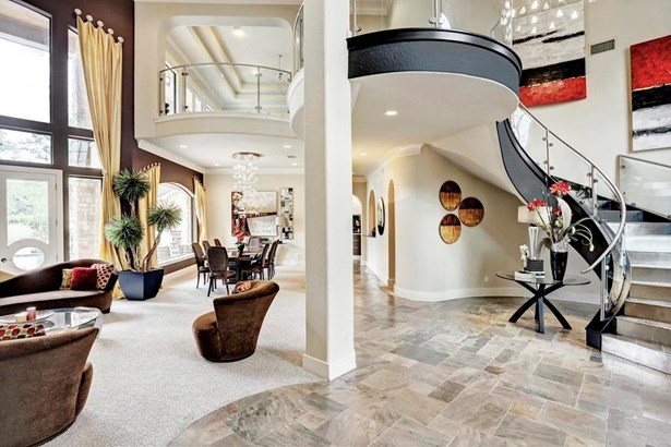 Guests enter your home to soaring ceilings, curved architecture and a winding staircase. (photo 4)