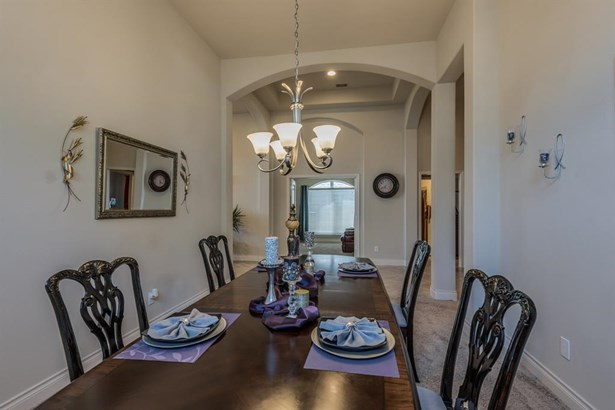 A view from the dining room toward the entry hall, with center up-light chandelier and a view of the softly arched openings which create special architectural appeal. (photo 4)