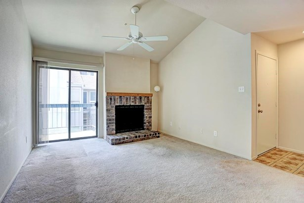 Spacious living room with vaulted ceilings and fireplace. Balcony located off living room. (photo 2)
