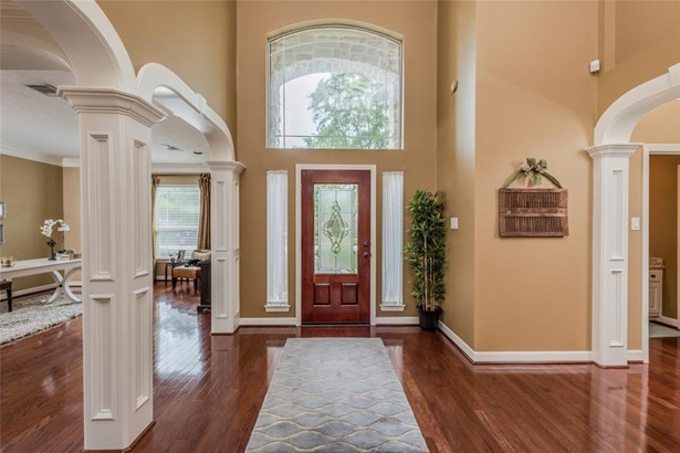 Gorgeous inside! Beautiful wood floors with graceful arched openings to the formal living and dining rooms on the left and the guest bedroom and master suite on the right. (photo 5)