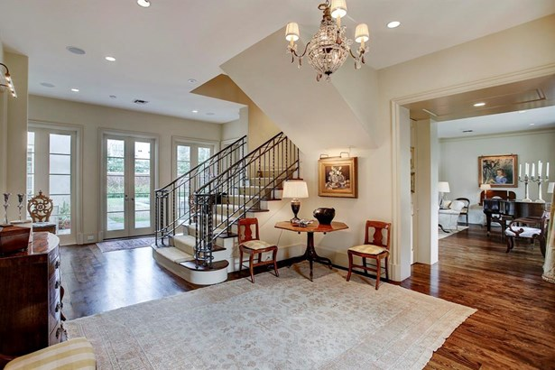 Another view of the large foyer with the center staircase. Through the doorway on the right enters into a very generously sized formal living room. Across the rear of the home are French doors and windows which shower the home's interiors with natural lig (photo 3)