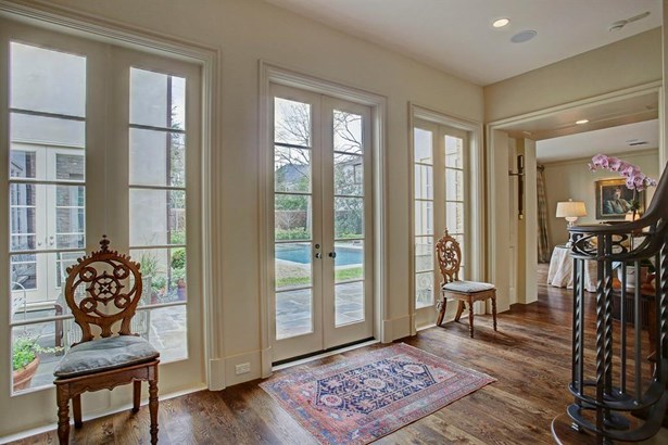 The gallery at the back of the entrance hall with French doors and windows looking out to a slate patio and beyond, a beautiful saltwater swimming pool. (photo 5)